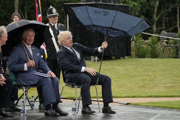 British Prime Minister Boris Johnson tries to open his umbrella next to Prince Charles at the dedication ceremony of the new national U.K. Police Memorial on July 28, 2021. (Photo: CHRISTOPHER FURLONG via Getty Images)