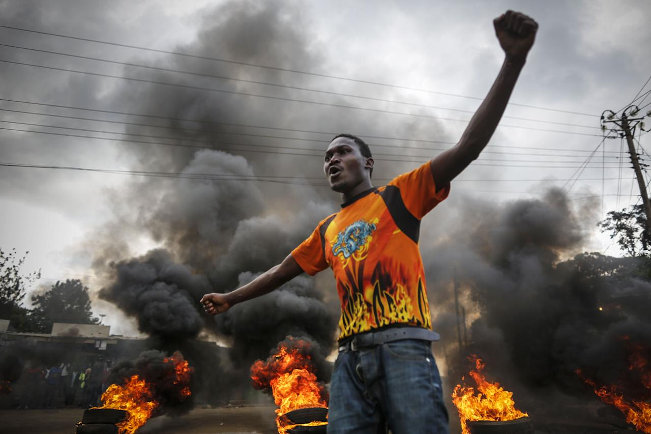 <p>A supporter of the opposition coalition the National Super Alliance (NASA) and its presidential candidate Raila Odinga reacts in front of a burning barricade he and others set up to block vehicles from delivering electoral materials to the polling stations in ther areas in Kibera slum, one of the opposition strongholds in Nairobi, Kenya, Oct. 25, 2017.(Photo: Dai Kurokawa/EPA-EFE/REX/Shutterstock) </p>
