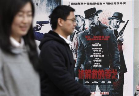 "People walk past a poster of the film ""Django Unchained"" outside a cinema in Beijing, April 11, 2013. REUTERS/Jason Lee/Files"