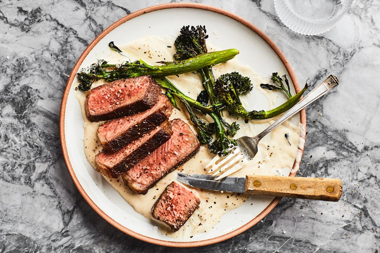 """If you like cheesy broccoli, you'll love this elevated but simple steak dinner that's drizzled with a creamy Gruyère sauce that equally complements both the steak and the crispy roasted broccolini. <a href=""""https://www.epicurious.com/recipes/food/views/charred-steak-and-broccolini-with-cheese-sauce?mbid=synd_yahoo_rss"""">See recipe.</a>"""
