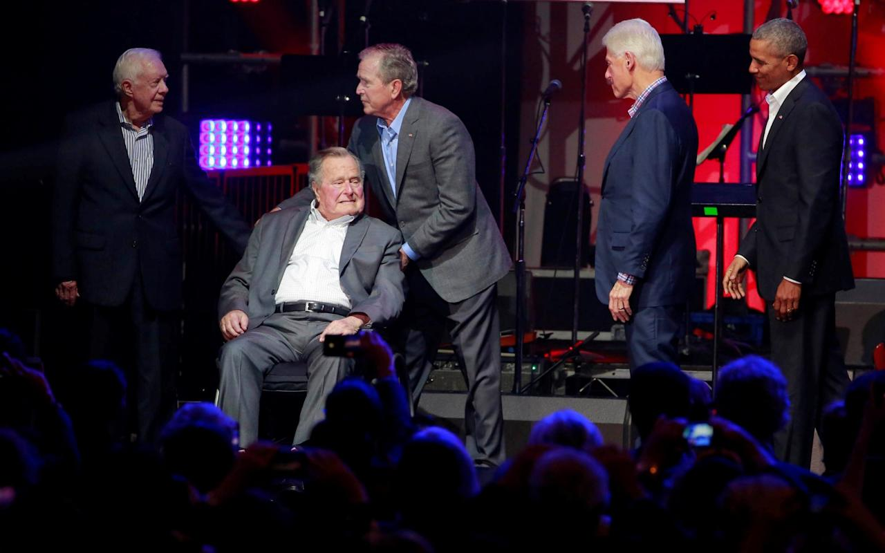 """The five living former presidents appeared together for the first time since 2013 on Saturday at a concert to raise money for victims of devastating hurricanes in Texas, Florida, Puerto Rico and the U.S. Virgin Islands. Democrats Barack Obama, Bill Clinton and Jimmy Carter and Republicans George H.W. and George W. Bush gathered on stage in College Station, Texas, home of Texas A&M University, putting aside politics to try to unite the country after the storms. Texas A&M is home to the presidential library of the elder Bush. At 93, he has a form of Parkinson's disease and appeared in a wheelchair at the event. His wife Barbara and George W. Bush's wife Laura Bush were in the audience. The concert features the country music band Alabama, Rock & Roll Hall of Famer 'Soul Man' Sam Moore, gospel legend Yolanda Adams and Texas musicians Lyle Lovett and Robert Earl Keen. Earlier on Saturday, President Donald Trump recorded a video greeting that avoids his past criticism of the former presidents and called them """"some of America's finest public servants."""" """"This wonderful effort reminds us that we truly are one nation under God, all unified by our values and devotion to one another,"""" Trump said in the message. The last time the five were together was in 2013, when Obama was still in office, at the dedication of George W. Bush's presidential library in Dallas. At a glance 