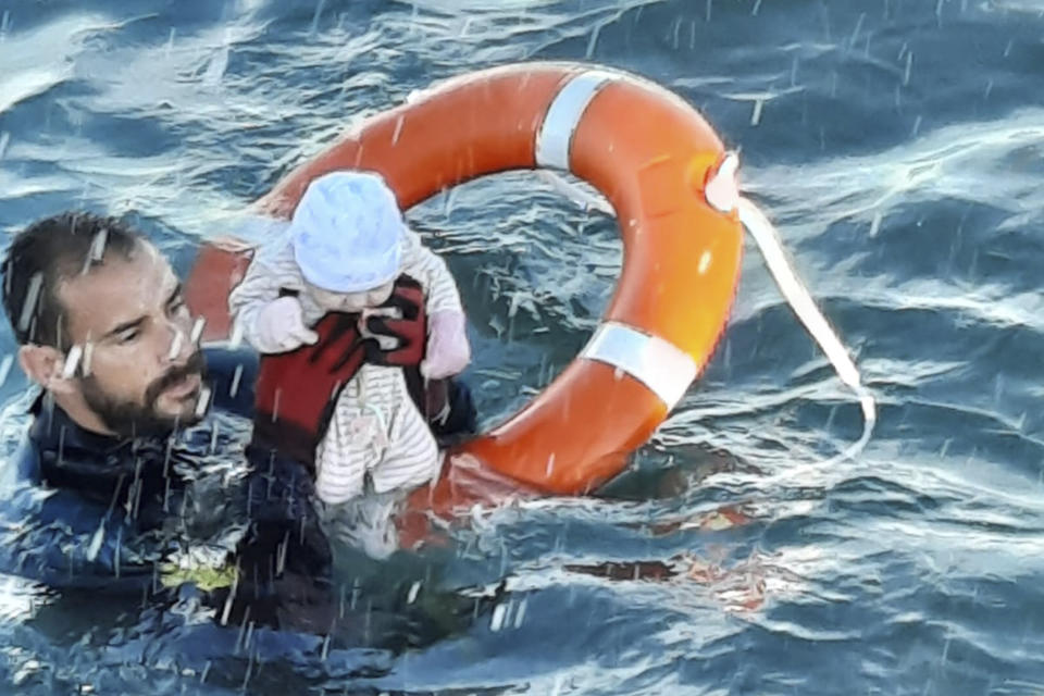 A member of the Spanish Civil Guard in Ceuta, Spain, rescues a baby that was separated from its parents, who were migrants. Source: Guardia Civil via AP