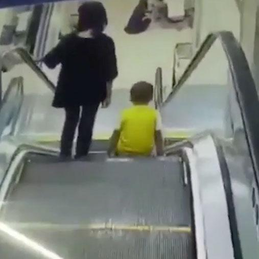 The boy takes a seat on the escalator next to his mum. Photo: AsiaWire