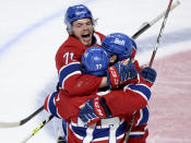 Montreal Canadiens' Alexander Romanov (27) celebrates his goal with teammates Jake Evans (71) and Brett Kulak (77) during the third period of Game 4 of the NHL hockey Stanley Cup final against the Tampa Bay Lightning in Montreal, Monday, July 5, 2021. (Ryan Remiorz/The Canadian Press via AP)