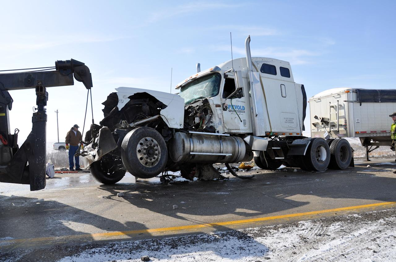 A crushed semi-trailer is towed on Highway 20, Monday, March 5, 2012, after chain-reaction collisions occurred involving nearly two-dozen vehicles near Webster City, Iowa. Authorities are blaming the pileups on poor visibility due to fog and thick, black smoke billowing from burning hay bales nearby. Eight people were hospitalized, two are reportedly in serious condition. (AP Photo/The Messenger, Jessie Helling)