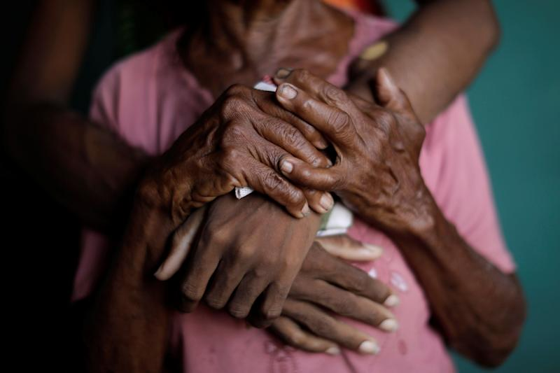 The hands of Aidalis Guanipa, 25, a kidney disease patient, and her 83-year-old grandmother, are seen as the two women pose for a photo; the women waiting for the electricity to return at Guanipa's house during a blackout in La Concepción, Venezuela. (Photo: Ueslei Marcelino/Reuters)