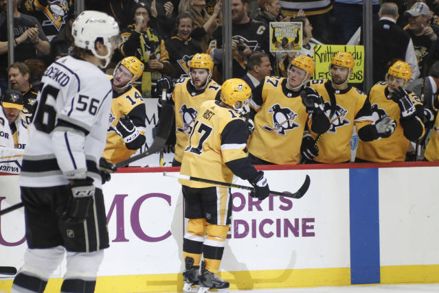Pittsburgh Penguins' Bryan Rust (17) is greeted by teammates on the bench after scoring his second goal of the period against the Los Angeles Kings during the second period of an NHL hockey game, Saturday, Dec. 14, 2019, in Pittsburgh. Kings' Kurtis MacDermid (56) skates by. (AP Photo/Keith Srakocic)