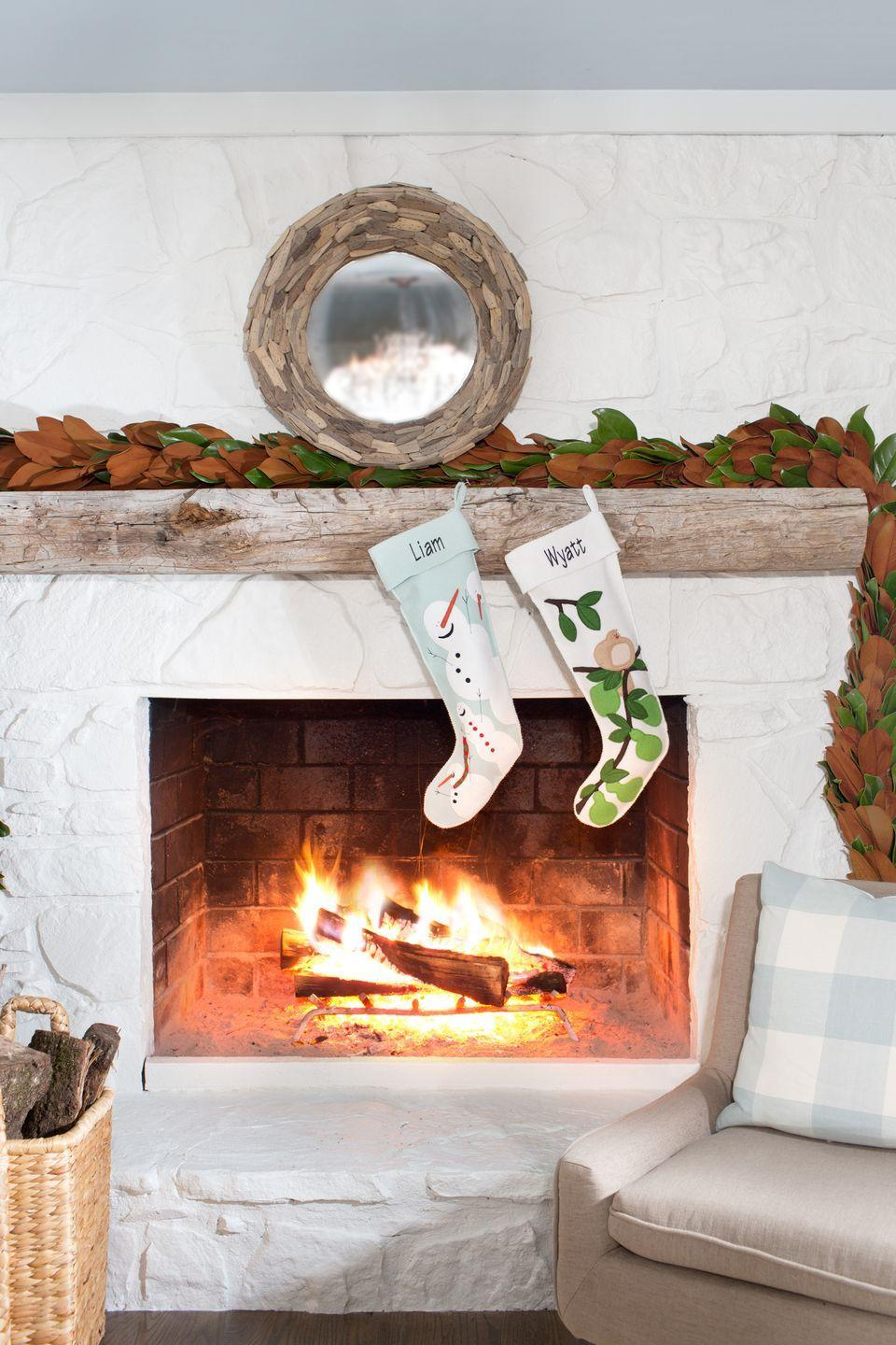 """<p>Personalized stockings add a fun element to an all-white fireplace. </p><p><a class=""""link rapid-noclick-resp"""" href=""""https://www.amazon.com/s/ref=nb_sb_noss?url=search-alias%3Daps&field-keywords=felt+christmas+garland&rh=i%3Aaps%2Ck%3Afelt+christmas+garland&tag=syn-yahoo-20&ascsubtag=%5Bartid%7C10050.g.1407%5Bsrc%7Cyahoo-us"""" rel=""""nofollow noopener"""" target=""""_blank"""" data-ylk=""""slk:SHOP FELT GARLAND"""">SHOP FELT GARLAND</a></p>"""