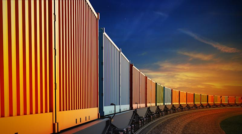 A freight train moving with the sunset in the background.