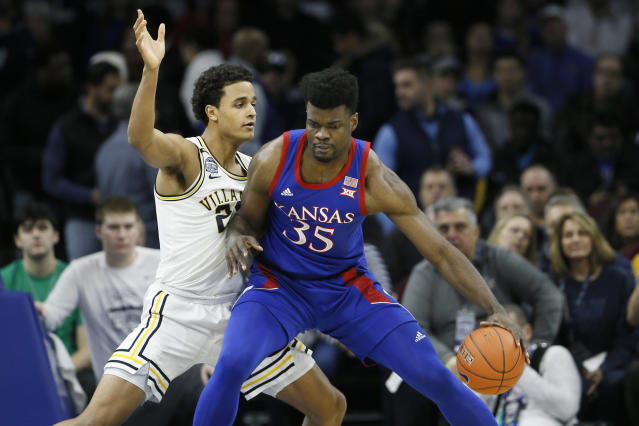 Kansas's Udoka Azubuike (35) tries to dribble past Villanova's Jeremiah Robinson-Earl (24) during the first half of an NCAA college basketball game, Saturday, Dec. 21, 2019, in Philadelphia. (AP Photo/Matt Slocum)