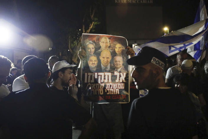 """Israeli police officers stand guard as right wing protesters chant slogans and hold signs showing Naftali Bennett, and other members of the Yamina party, with Arab politicians Ahmad Tibi, right, and Mansour Abbas, left, during a demonstration in the central Israeli city of Ramat Gan, Wednesday, June 2, 2021. Hebrew sign reads, """"Don't form a left government with supporters of terror."""" (AP Photo/Sebastian Scheiner)"""