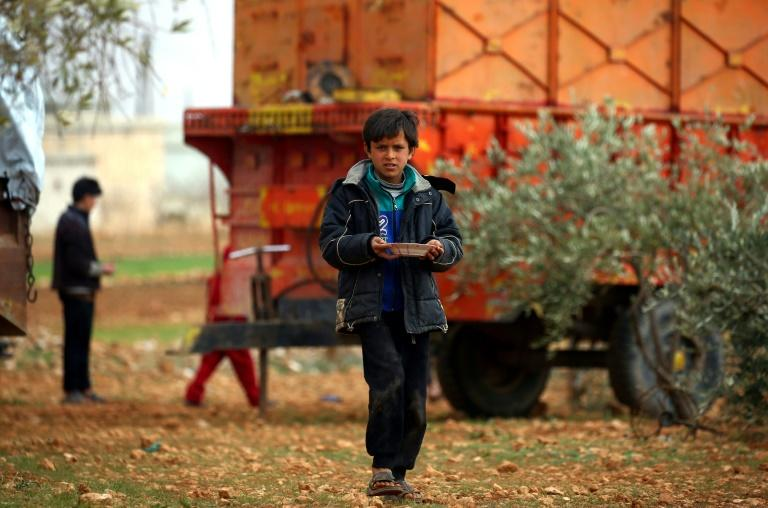 A displaced Syrian boy walks with a plate in Kharufiyah, 18 kilometres south of Manbij, on March 4, 2017