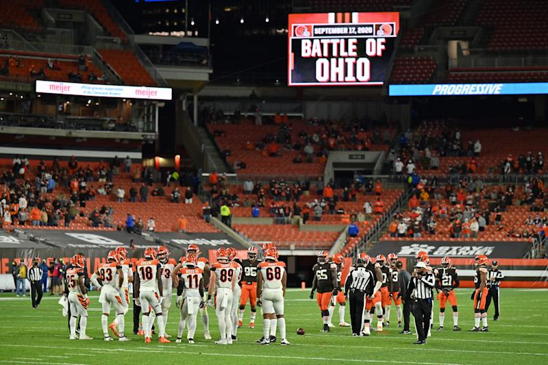 """Bengals and Browns players on the field with limited fans and """"Battle of Ohio"""" written on the corner videoboard."""