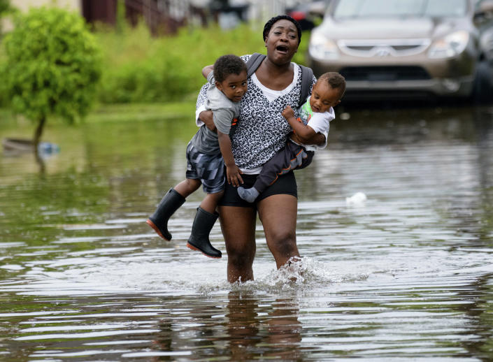 Terrian Jones reacts as she feels something moving in the water at her feet as she carries Drew and Chance Furlough to their mother on Belfast Street in New Orleans during flooding from a storm in the Gulf Mexico that dumped lots of rain, July 10, 2019. (Photo: Matthew Hinton/AP)