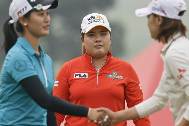 FILE - In this Oct. 5, 2013 file photo, South Korea's Inbee Park watches as China's Lin Xiyu, left, shakes hands with South Korea's Na Yeon Choi after they finished the 18th green during the third round of the Reignwood LPGA Classic golf tournament at Pine Valley Golf Club on the outskirts of Beijing, China. it's hard to find a South Korean who doesn't speak English with great proficiency _ in pro-ams, in interviews, speeches, even with other players. That so-called problem of the LPGA Tour being taken over by South Koreans sure doesn't seem like one anymore. (AP Photo/Alexander F. Yuan, File)