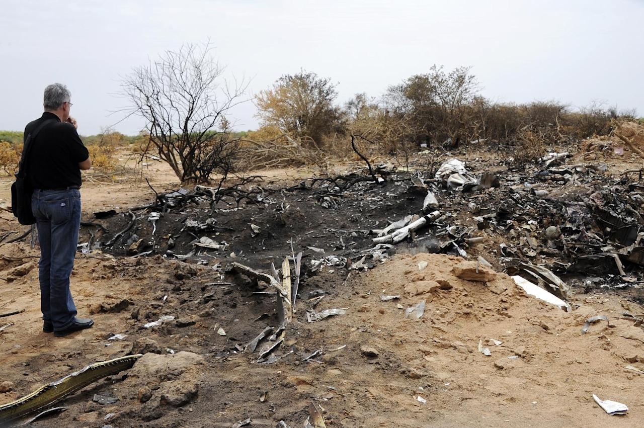 A representative of the Lebanese victims' relatives looks at debris at the crash site of the Air Algerie Flight AH 5017 in Mali's Gossi region, west of Gao, on July 26, 2014 (AFP Photo/Sia Kambou )