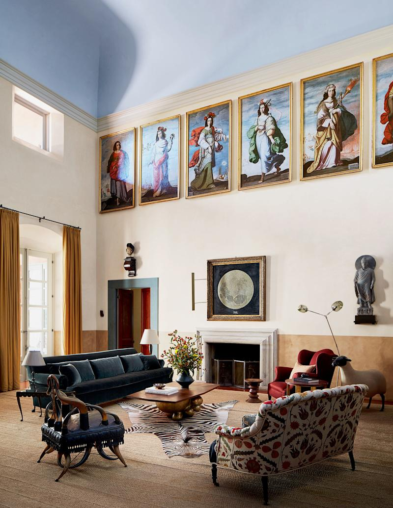 In the wainscot–wrapped great room, an Alma Allen cocktail table, BDDW sofa in a Kerry Joyce mohair velvet, wingback chair, and love seat form a seating area. Les Lalanne sheep; custom rug by Hechizoo Textiles.