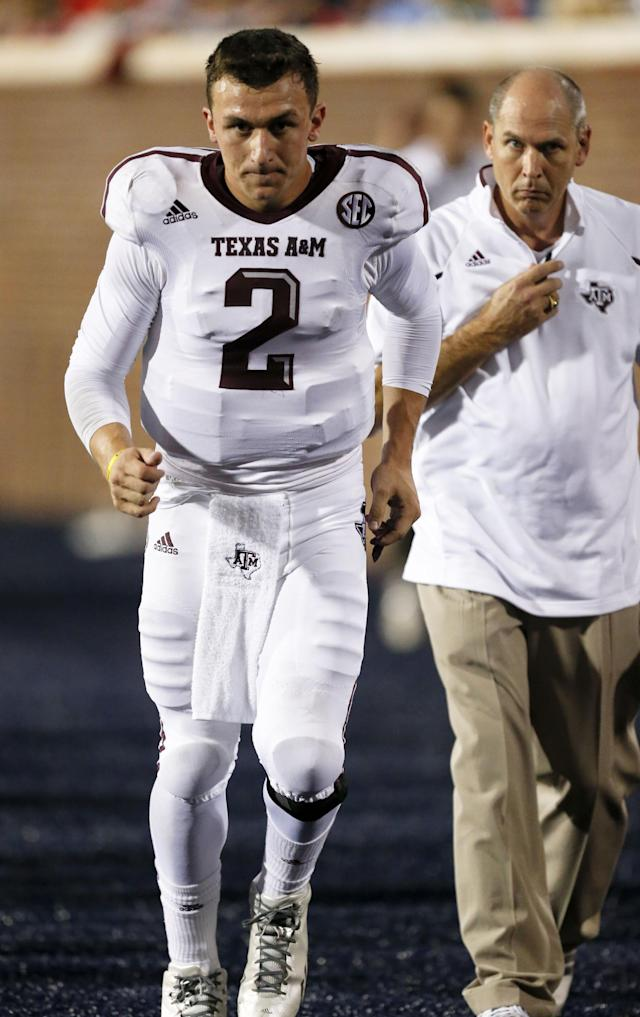 Texas A&M quarterback Johnny Manziel (2) tests his knee as a trainer watches before getting back to the game in the first half of their NCAA college football game against Mississippi at Vaught-Hemingway Stadium in Oxford, Miss., Saturday, Oct. 12, 2013. (AP Photo/Rogelio V. Solis)