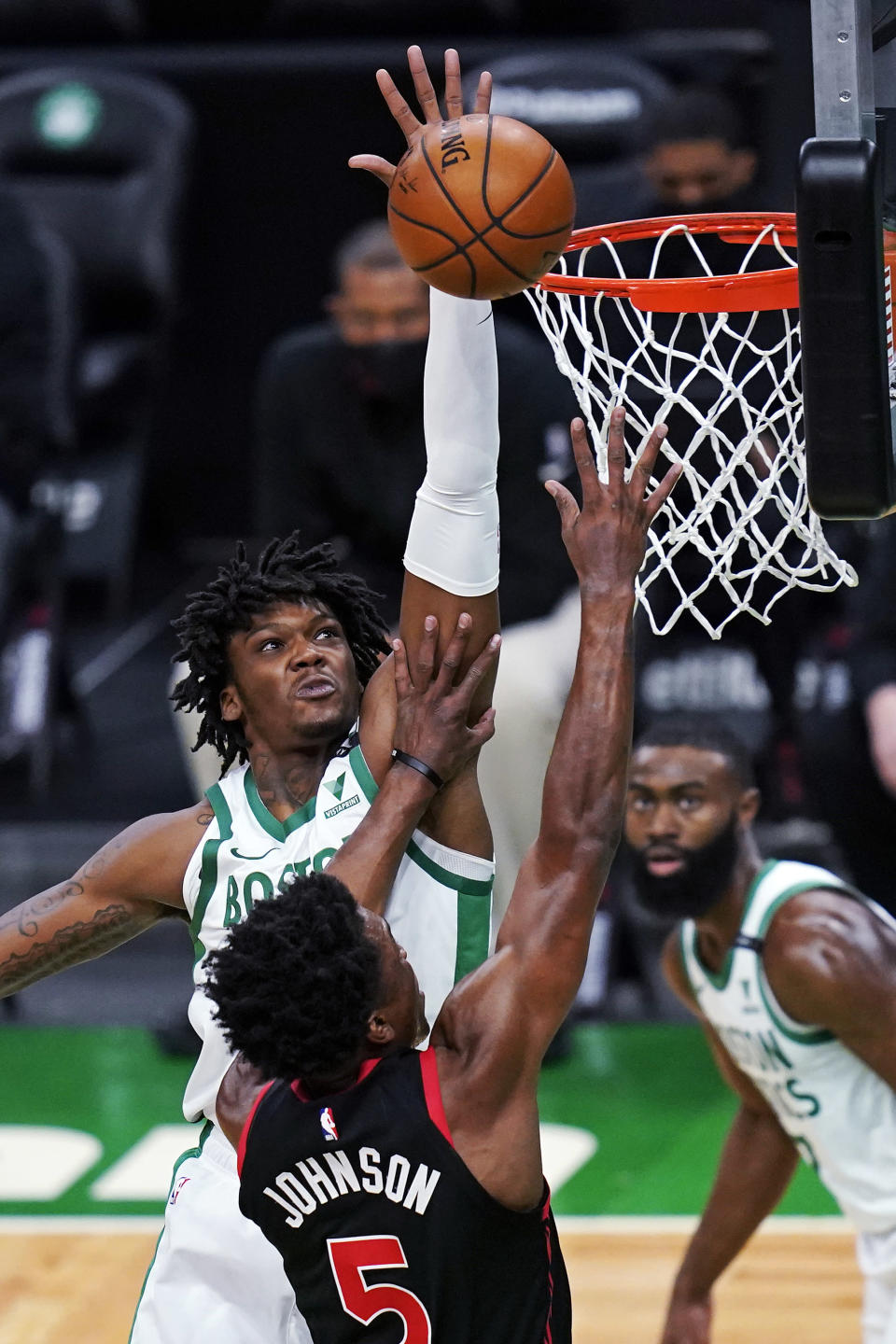 Boston Celtics center Robert Williams III, left, reaches high blocking a shot by Toronto Raptors forward Stanley Johnson (5) during the first half of an NBA basketball game, Thursday, March 4, 2021, in Boston. (AP Photo/Charles Krupa)