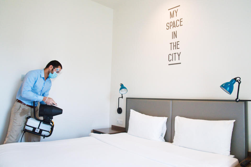 An employee wearing a mask due to the coronavirus pandemic fogs disinfectant in a hotel room at the Rove City Centre Hotel in Dubai, United Arab Emirates, Monday, July 6, 2020. Dubai reopened for tourists Tuesday amid the coronavirus pandemic, hoping to reinvigorate a vital industry for this city-state before its crucial winter tourist season. (AP Photo/Jon Gambrell)