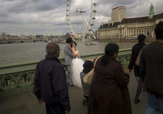 Newlyweds pose for photographs on Westminster Bridge in London March 10, 2012.