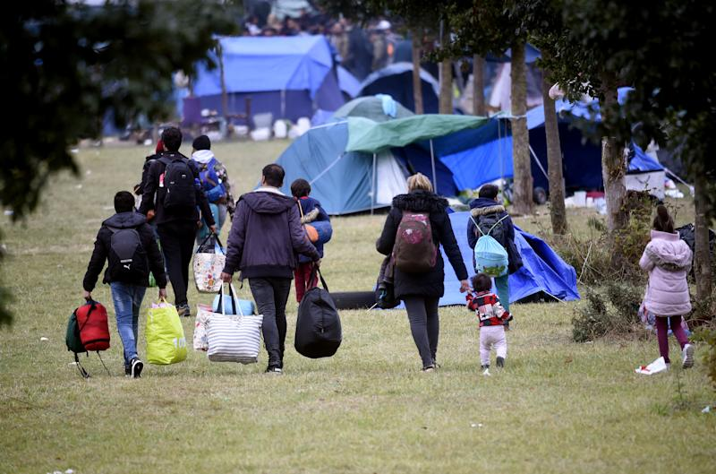 Migrant families leave the camp with their belongings during an evacuation by French police
