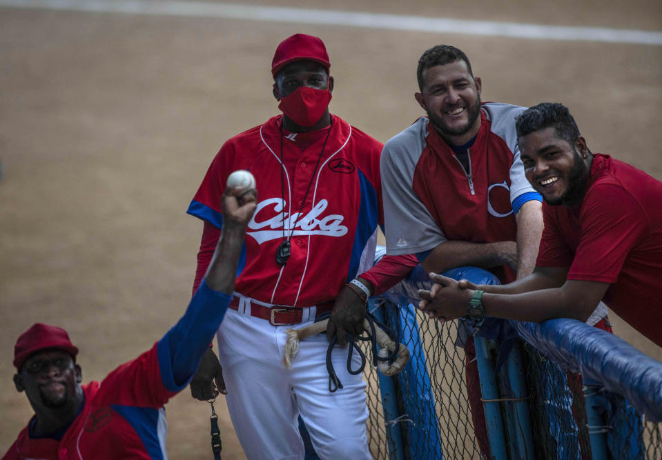 Cuba's pitcher Yoanni Yera Montalvo, left, throws the ball as his teammates smile watching him during a training session at the Estadio Latinoamericano in Havana, Cuba, Tuesday, May 18, 2021. A little over a week after the start of the Las Americas Baseball Pre-Olympic in Florida, the Cuban team does not have visas to travel to the United States. (AP Photo/Ramon Espinosa)