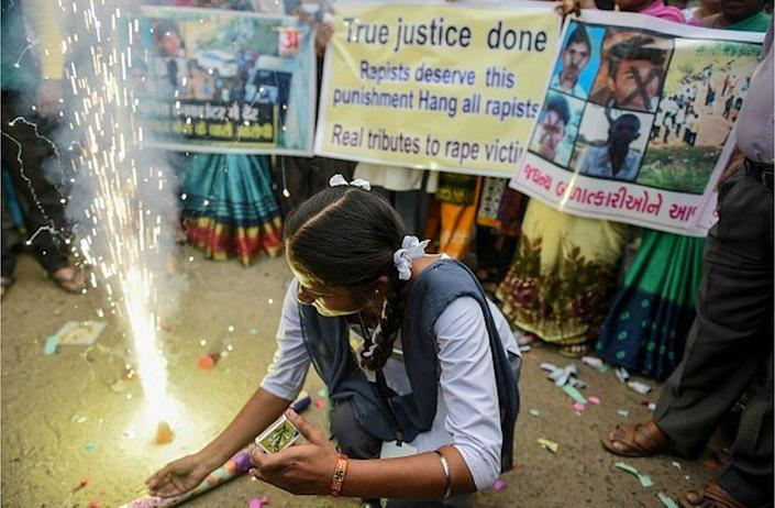 A schoolgirl in Ahmedabad lights firecrackers after police killed four gang-rape and murder suspects in Hyderabad on December 6, 2019