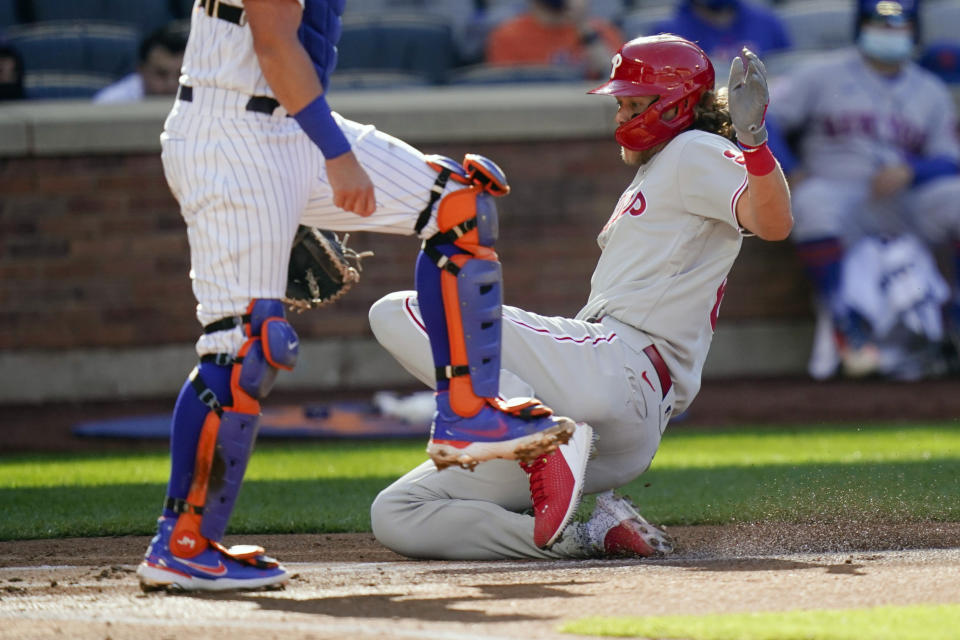 Philadelphia Phillies' Alec Bohm slides past New York Mets catcher James McCann to score on a sacrifice fly ball by Andrew Knapp during the second inning of a baseball game in the first game of a doubleheader Tuesday, April 13, 2021, in New York. (AP Photo/Frank Franklin II)