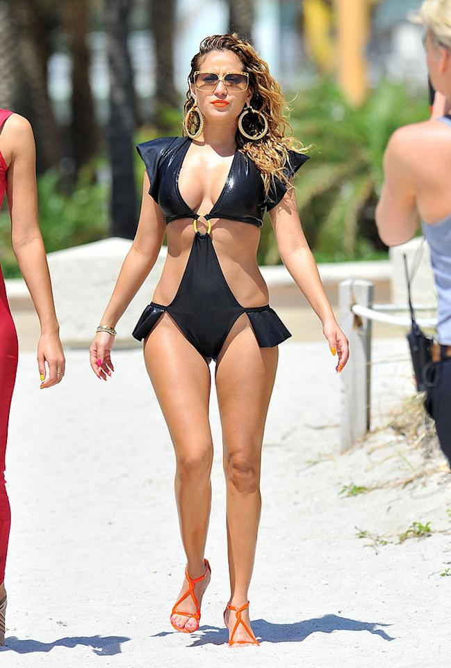 "Former Cheetah Girl Adrienne Bailon left little to the imagination in skimpy swimwear while filming her new reality show, ""Empire Girls,"" in South Beach late last week. The 28-year-old's attention-seeking suit featured trash bag-like fabric, shoulder shields, and hip flaps. Bright orange lipstick, gold sunglasses, and matching door knocker earrings made for equally atrocious accessories. What do you make of the Disney alumna's style snafu? Heinous or hot? (4/26/2012)<br><br><a target=""_blank"" href=""http://bit.ly/lifeontheMlist"">Follow What Were They Thinking?! creator, Matt Whitfield, on Twitter!</a>"