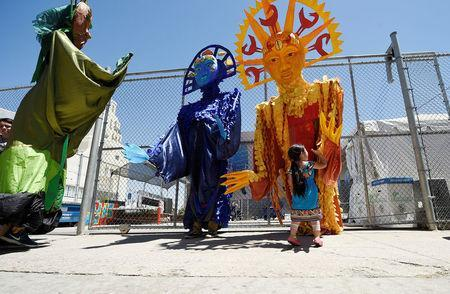 A girl high fives Sun, Moon and Tree puppets after they marched from the intersection of Florence and Normandie Avenue, the flashpoint where the riots started 25 years ago, to remember and honor the victims of the 1992 Los Angeles riots in Los Angeles, California, U.S., April 29, 2017. REUTERS/Kevork Djansezian