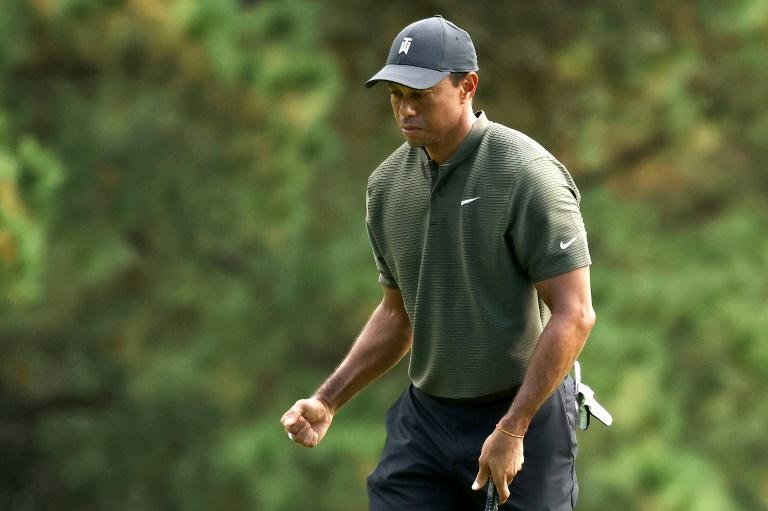 Defending champion Tiger Woods pumps his fist after making a putt in Thursday's opening round of the 84th Masters