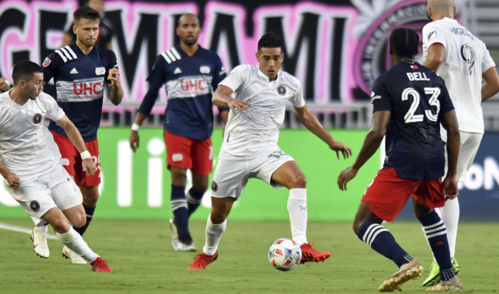 Inter Miami midfielder Victor Ulloa (13) looks to bring the ball up the field as New England Revolution defender Jon Bell (23) defends during the first half of an MLS soccer match Wednesday, July 21, 2021, in Fort Lauderdale, Fla. (AP Photo/Jim Rassol)
