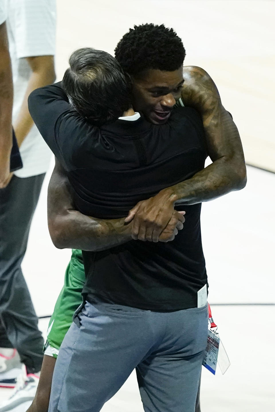 North Texas's Javion Hamlet hugs head coach Grant McCasland celebrates after North Texas defeated Purdue, 78-69, in overtime of a first-round game in the NCAA men's college basketball tournament at Lucas Oil Stadium, Friday, March 19, 2021, in Indianapolis. (AP Photo/Darron Cummings)