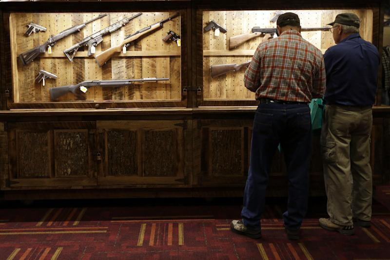 Attendees look over a wall of guns available to win in a raffle at the National Rifle Association's annual convention in Friday, April 25, 2014 in Indianapolis. Several potential Republican contenders for president will court gun-rights supporters at the NRA's annual convention Friday. (AP Photo/AJ Mast)