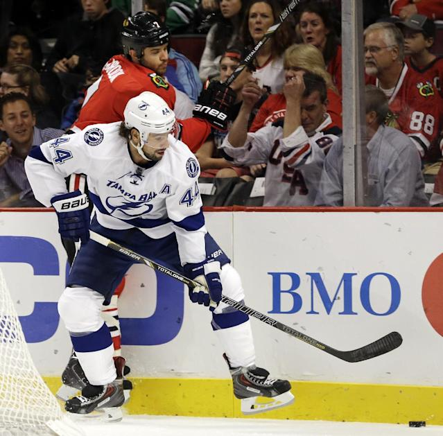 Tampa Bay Lightning's Nate Thompson (44) checks Chicago Blackhawks' Brent Seabrook during the first period of an NHL hockey game in Chicago, Saturday, Oct. 5, 2013. (AP Photo/Nam Y. Huh)