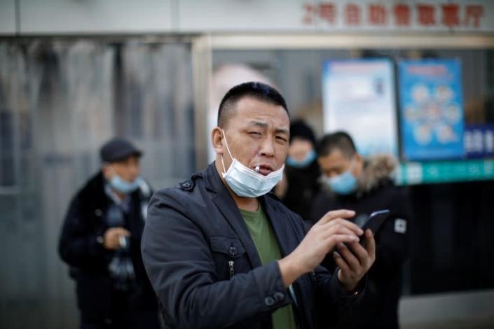A man wearing a face mask uses his cellphone while smoking outside Beijing Railway Station as the country is hit by an outbreak of the new coronavirus, in Beijing