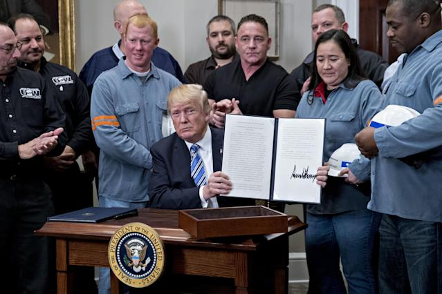 President Trump holds up a signed proclamation on adjusting tariffs on imports of steel into the United States, flanked by steel and aluminum workers in the Roosevelt Room of the White House on March 8, 2018. (Photo: Andrew Harrer/Bloomberg via Getty Images)