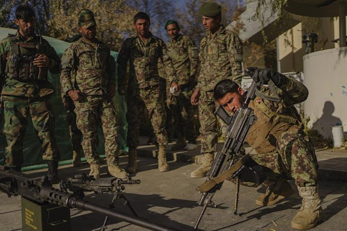 Soldiers inspect and clean their weapons.