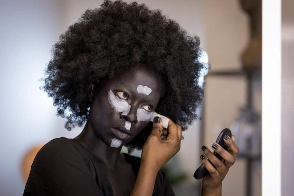 Glow Up's Dolli, a Black woman, who has painted her face a darker shade of brown, and is applying white stripes