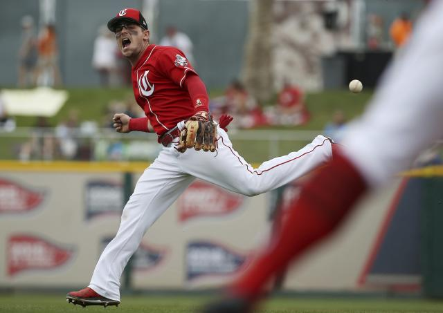 Cincinnati Reds second baseman Scooter Gennett shouts as he is unable to make a bare-handed grab on an infield hit by Kansas City Royals' Humberto Arteaga during the fourth inning of a spring training baseball game Thursday, March 21, 2019, in Goodyear, Ariz. (AP Photo/Ross D. Franklin)
