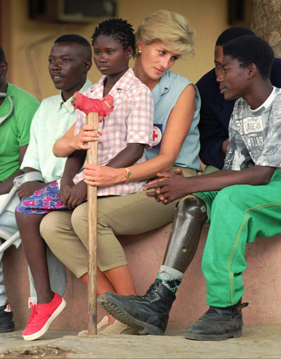 """FILE - In this Tuesday, Jan. 14, 1997 file photo, Diana, Princess of Wales, talks to amputees, at the Neves Bendinha Orthopedic Workshop in the outskirts of Luanda. For someone who began her life in the spotlight as """"Shy Di,"""" Princess Diana became an unlikely, revolutionary during her years in the House of Windsor. She helped modernize the monarchy by making it more personal, changing the way the royal family related to people. By interacting more intimately with the public -- kneeling to the level of children, sitting on edge of a patient's hospital bed, writing personal notes to her fans -- she set an example that has been followed by other royals as the monarchy worked to become more human and remain relevant in the 21st century. (AP Photo/Joao Silva, File)"""