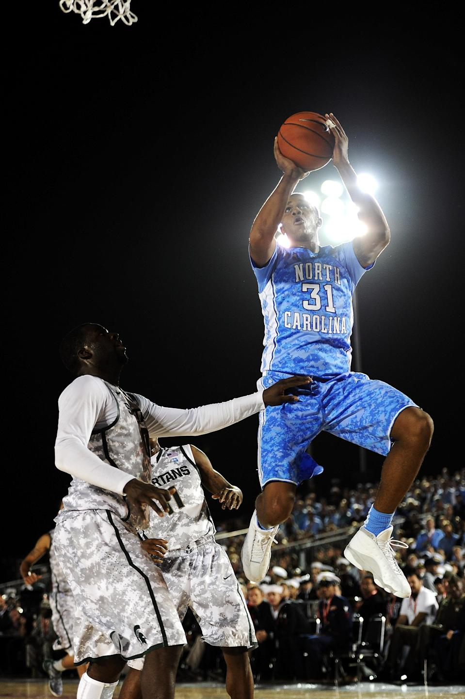 SAN DIEGO, CA - NOVEMBER 11: John Henson #31 of the North Carolina Tar Heels makes a move to the basket against Draymond Green #10 of the Michigan State Spartans in the first half during the NCAA men's college basketball Carrier Classic aboard the flight deck of the USS Carl Vinson on November 11, 2011 in San Diego, California. (Photo by Harry How/Getty Images)