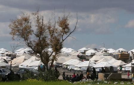Internally displaced people, who fled with others Raqqa city, stand outside tents at a camp in Ain Issa