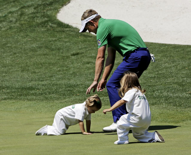 Luke Donald, of England, picks up his youngest daughter Sophia while Elle Donald, right, plays on a green during the par three competition at the Masters golf tournament Wednesday, April 9, 2014, in Augusta, Ga. (AP Photo/David J. Phillip)
