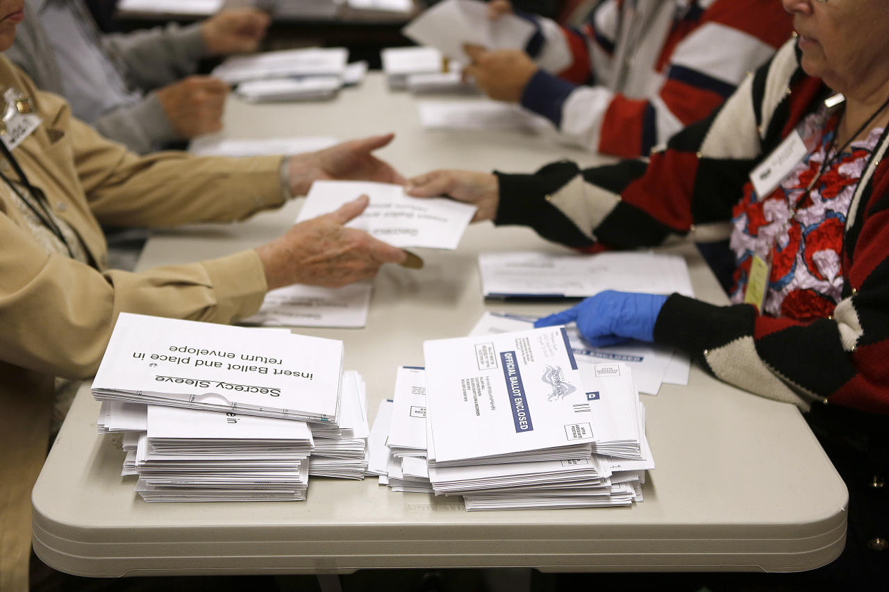 Election workers open mail-in ballots at the Boulder County Clerk and Recorder's Office on November 6, 2012 in Boulder, Colorado. Colorado is considered by most experts to be a key battleground state in this year's election. (Photo by Marc Piscotty/Getty Images)