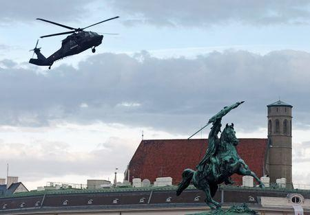 "An Austrian army Sikorsky S-70 ""Black Hawk"" helicopter hovers over a statue of Archduke Charles as it lands in Vienna"