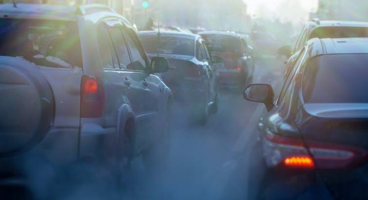 A traffic jam of cars surrounded by smoke.