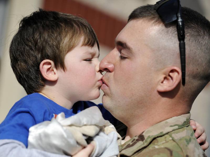 Capt. Matt Lovelace, right, kisses his son, Jackson Lovelace, 2, during a deployment ceremony for the South Carolina Army National Guard 3/49 Agribusiness Development Team at McCrady Training Center, Thursday, Jan. 10, 2013, at Ft. Jackson, S.C. The deployment is scheduled for a year including a one month of training in Indiana prior to leaving for Afghanistan. (AP Photo/Rainier Ehrhardt)