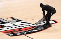 Workers remove decals from the court after the cancelation of the 2020 Atlantic 10 men's basketball tournament prior to the second round at Barclays Center on March 12, 2020 in the Brooklyn borough of New York City. The tournament was canceled amid growing concerns of the spread of COVID-19 (Coronavirus.) (Photo by Mike Lawrie/Getty Images)